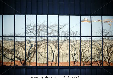 The abstract reflection of a house facade with windows in another house facade with windows.