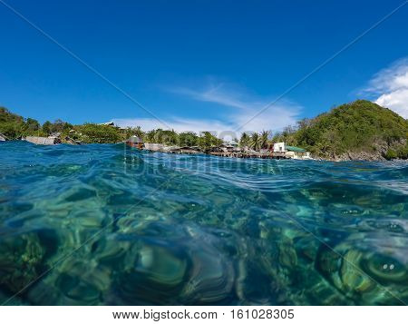 Sea water and beach natural double landscape. Look through seawater. Clean sea lagoon with underwater coral reef and green beach. Clear blue sky above tropical island. Waterline with underwater image