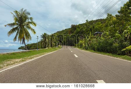 Highway on tropical island. Coastal road in the afternoon. Empty road by the seaside. Green hill beach coco palm tree on the roadside. Forest and sea landscape. Summer holiday travel image or banner