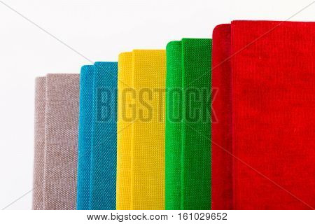 Multicolored book textile cover. Photobooks on a white background