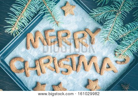 Phrase Merry Christmas from homemade gingerbread cookies on dark wooden background. Christmas cookies concept. Christmas moody style greetings card. Happy New Year. Top view.