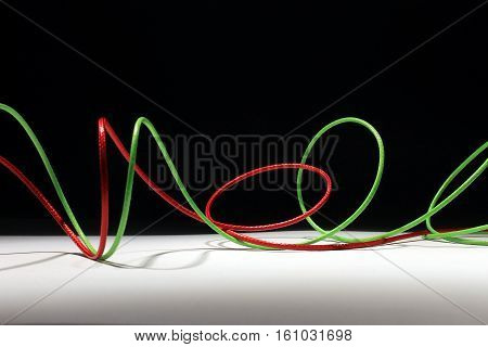 Red and green wires that twists on a black and white background.
