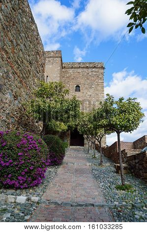 Towers of Alcazaba with orange trees and flowers near Gibralfaro Castle - Malaga in Andalusia Spain