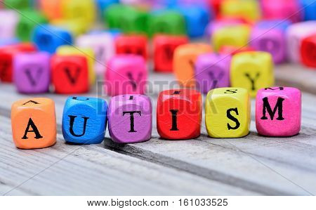 Autism word on grey wooden table closeup