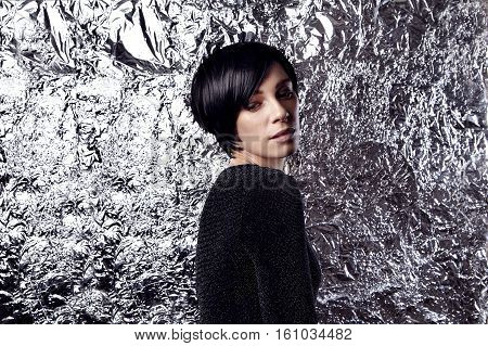 Portrait of sexy woman with short black hair party look. Glitter and silver background.