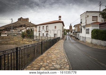 a street in La Calahorra town and the ancient Castle-Palace on a cloudy day, Province of Granada, Spain
