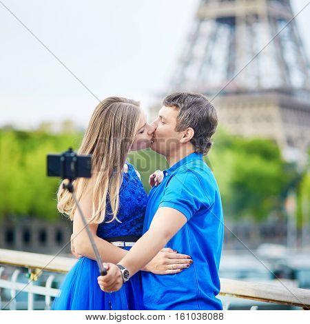 Couple In Paris Making Selfie Using Selfie Stick Near The Eiffel Tower