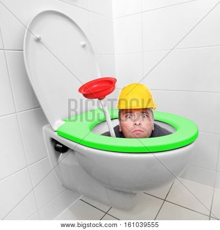 Funny repairman looking from toilet bowl with green seat in a modern bathroom. Homemade production of biomass and biogas. Environmentally friendly life in European Union.