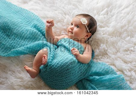 An alert six week old baby girl swaddled in a turquoise blue scarf and lying on a flokati rug.