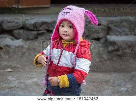 SIKKIM, INDIA - DECEMBER 03, 2016: Cute expression of Indian kid in winter wear at Lachung, Sikkim, India.