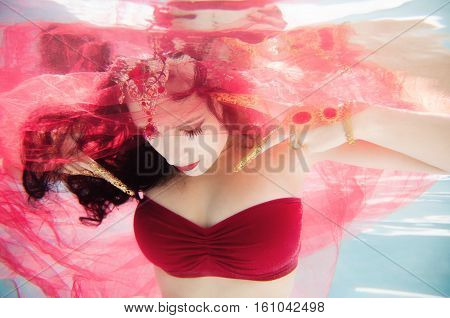 An artistic underwater portrait of a female model wearing a red bandeau top gold Thai fingernails and a jewel headpiece. She is shrouded in red tulle.