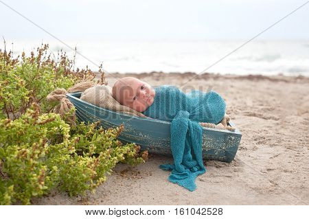 Three week old newborn baby boy swaddled in a blue wrap and sleeping in a tiny wooden boat. Photographed at the ocean with sand and beach vegetation.