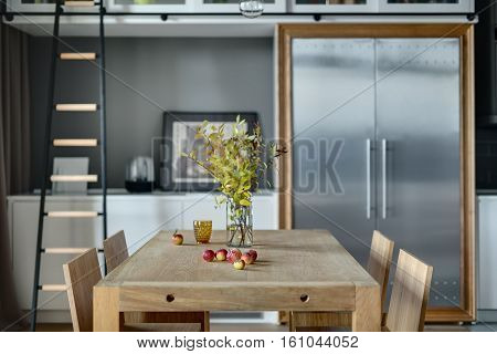 Light wooden table with branches in the vase, apples, glass and  four chairs in the modern kitchen. There is white lockers, dark ladder, lamp, trendy big fridge with two doors. Wide aperture photo.