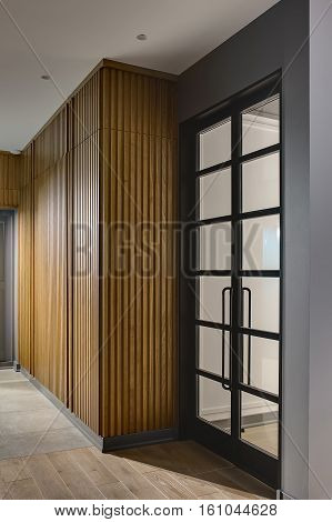 Glowing hall in a modern style with gray walls and tiles with a parquet on the floor. There is a large wooden wardrobe, gray door and glass black door. Vertical.