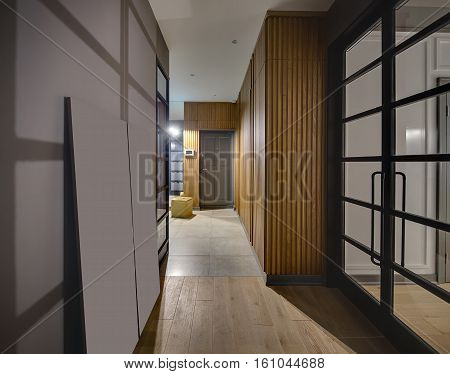 Hallway in a modern style with glowing lamps and gray walls. On the floor there are tiles and a parquet. There is a large wooden wardrobe, gray door, yellow pouf and glass black doors. Vertical.