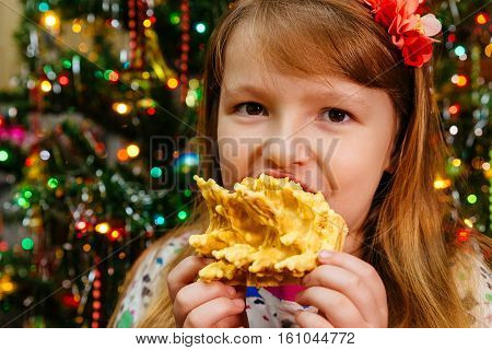 cute little beautiful girl eats cake sakotis new year and merry christmas background
