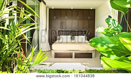 Modern bedroom with two pillows cover with a glass which exposed to the outside area garden with fancy pants
