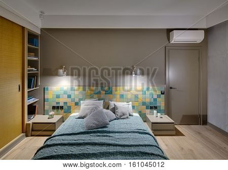 Bedroom in a modern style with a large bed with many pillows and a coverlet on the colorful tiles background. There are two wooden nightstands, glowing lamps, shelves with books, wooden wardrobe.