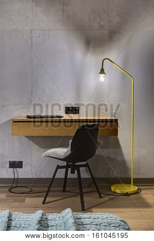 Wooden rack with a laptop and a black chair with a gray pillow on the background of the gray tiled wall. Next to the rack there is a glowing trendy yellow lamp. Black power sockets are on the wall.