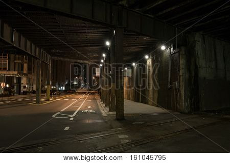 Dark urban downtown city elevated train tunnel and street at night.