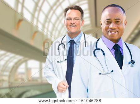 African American and Caucasian Male Doctors Inside Hospital Office.