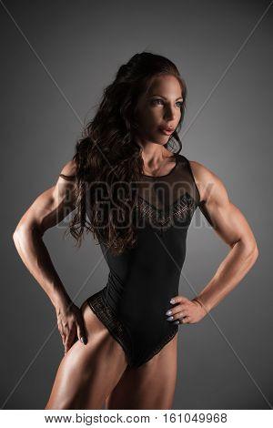 Sexy long haired curly brunnette in black underwear posing in studio