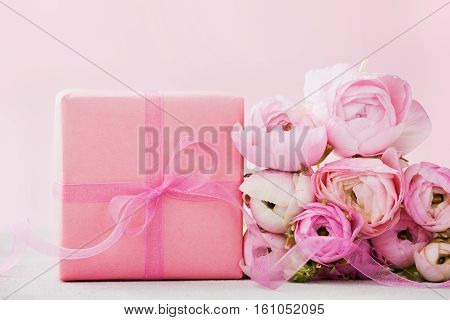 Beautiful spring Ranunculus flowers and gift box on gray stone background. Pastel color. Greeting card for Valentines or Womans Day. Empty space for text.