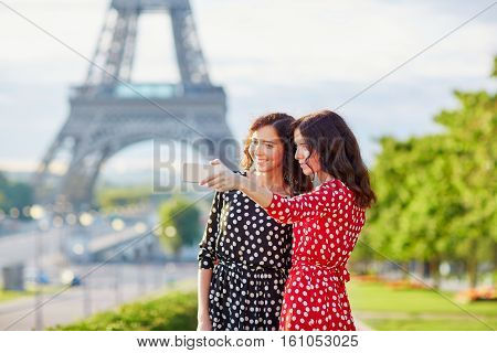 Beautiful Twin Sisters Taking Selfie In Front Of Eiffel Tower