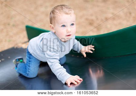 adorable toddler being playful at the slide enjoying time at the playground
