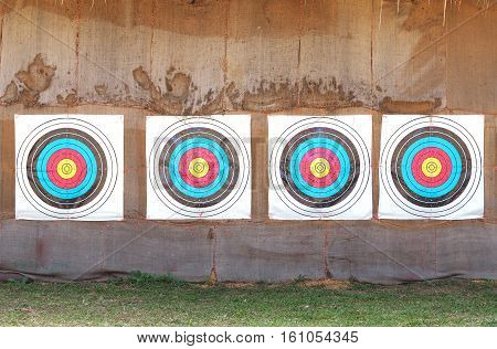 Row of four archery target rings on old brown fabric background.