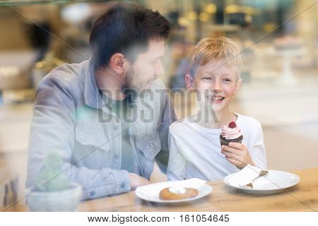 father and son enjoying time together in cafe eating desserts through the window