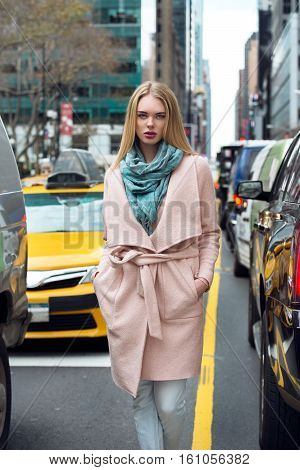 Beautiful elegant blonde business woman walking out from the taxi on New York City street and walk throught the traffic wearing elegant pink jacket with scarf.