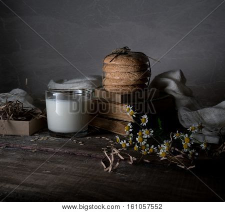 vintage. old books, a glass of milk, cakes, drapery on a wooden table
