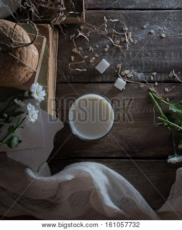 vintage. old books, a glass of milk, cakes, drapery on a wooden table. top view