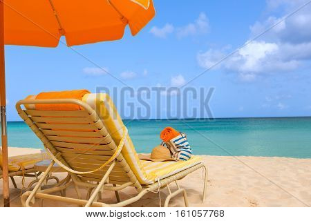 sunbeds with beach accessories and umbrella at picture perfect caribbean beach