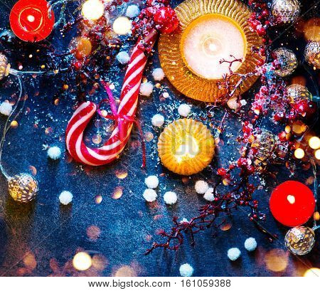 Christmas Holiday Background with Candy Cane, decorations, candles, garland and evergreens border over dark background table. Christmas and New year food. Xmas dinner, served table, decorations