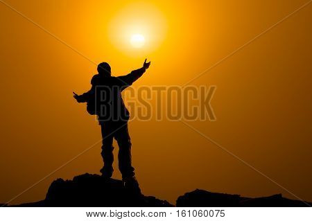 Man with arms extended toward heaven at sunrise , success or prayer concept warm tone