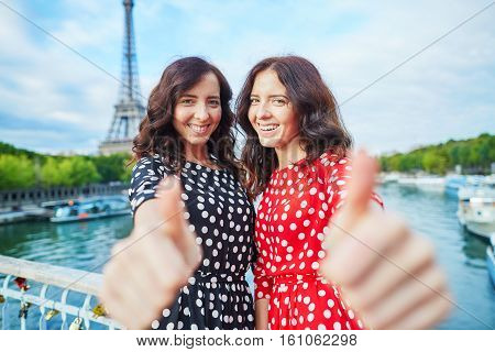 Cheerful Smiling Twin Sisters Showing Thumbs Up
