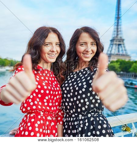Cheerful Smiling Twin Sisters Showing Thumbs Up In Front Of Eiffel Tower, Paris