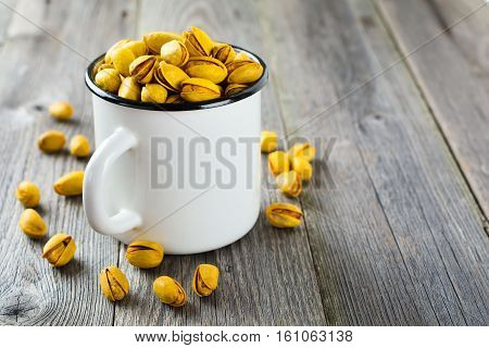 Salted pistachios with saffron in an iron cup. Selective focus.