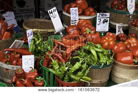 Many baskets full of red and green peppers at the outdoor/indoor Jean-Talon Market in Montreal, Quebec, on a bright day in September.