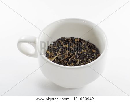 dry tea leaf in a cup on a white background