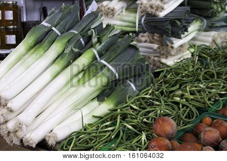 Bunches of stacked fresh green onions shallots at the outdoor/indoor Jean-Talon Market in Montreal, Quebec, on a bright day in September.