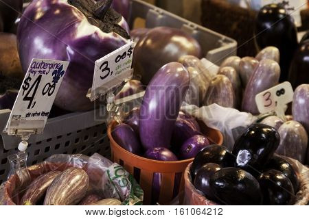 A large variety of eggplants in small baskets at the outdoor/indoor Jean-Talon Market in Montreal, Quebec, on a bright day in September.
