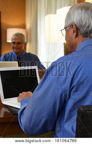 A senior businessman seated at the desk in his hotel room and working on his laptop computer. Vertical format with the mans reflection in the mirror.