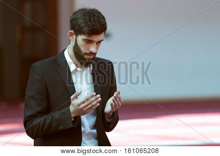 Younger Muslim man praying in colorful mosque.