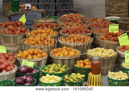 Large variety of fruits and vegetables in baskets and one jar of tamato sauce in front of an store at the outdoor/indoor Jean-Talon Market in Montreal, Quebec, on a bright day in September.