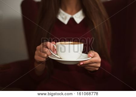 Closeup female hands holding a cup of coffee.