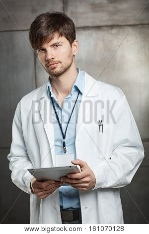 Young male doctor holding tablet computer, looking at camera.