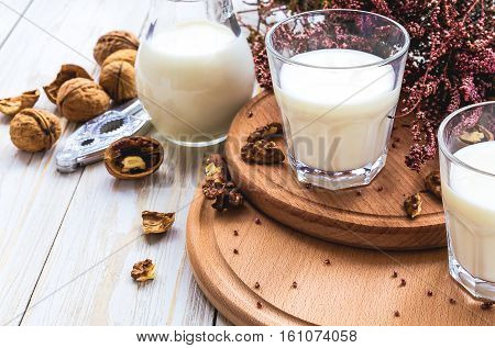 Milk, Heather Flowers And Walnuts. Wooden Table.